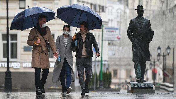 Прохожие во время дождя в Камергерском переулке в Москве
