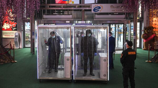 Посетители проходят через кабины дезинфекции при входе в торговый центр Европейский в Москве