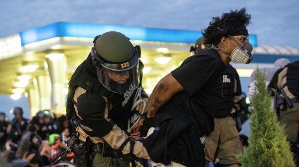 Сотрудник полиции задерживает участницу протеста в Миннеаполисе