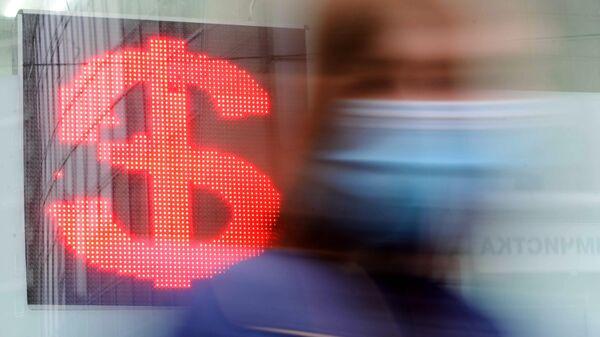 Женщина возле электронного табло с курсом валют в Москве