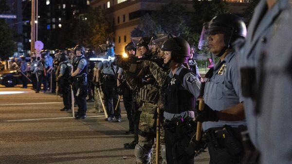 Сотрудники полиции и солдаты Национальной гвардии США выстроились в оцепление в Миннеаполисе после ареста протестующих