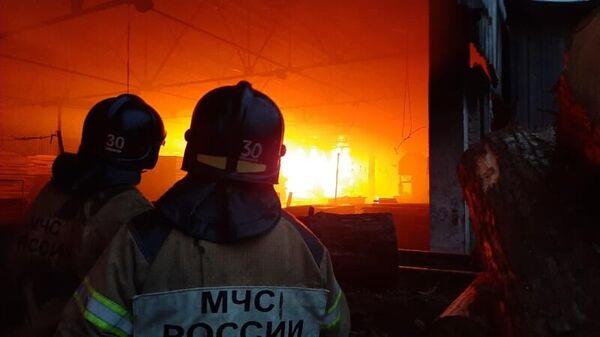 Сотрудник МЧС во время тушения пожара в складском помещении