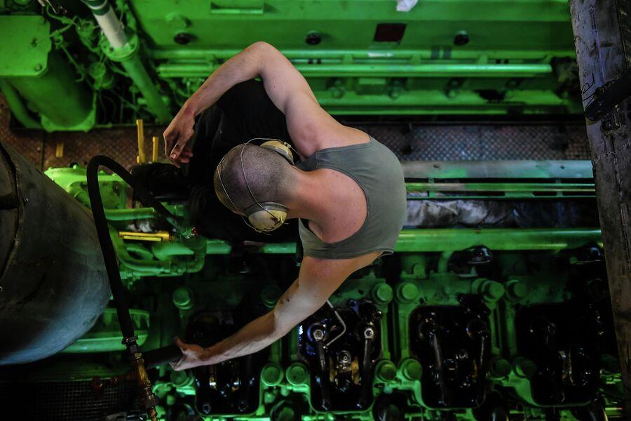 Моторист в машинном отделении ремонтирует один из двигателей