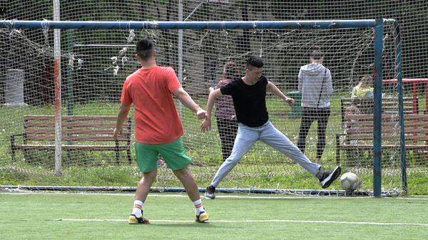 Молодые люди играют футбол на школьном стадионе