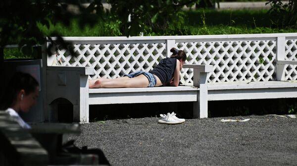 Девушка загорает в Парке Горького в Москве