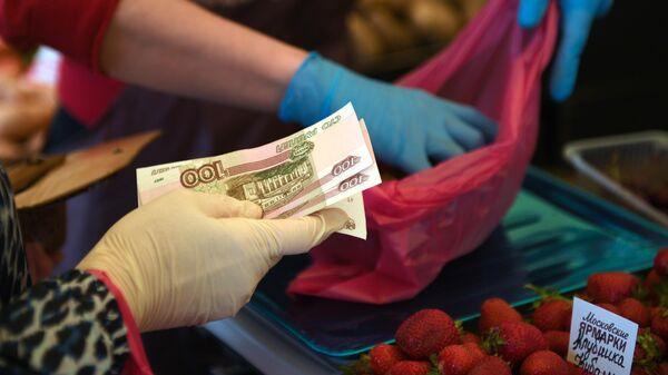 Женщина покупает клубнику