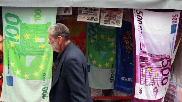 Мужчина проходит мимо киоска, торгующего полотенцами в виде банкнот евро в Афинах