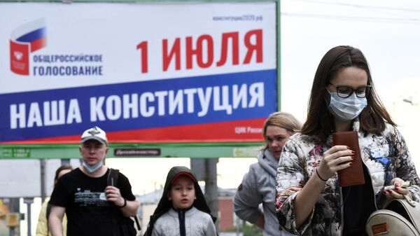 Прохожие около баннера, информирующего об общероссийском голосовании по поправкам в Конституцию РФ, в Новосибирске