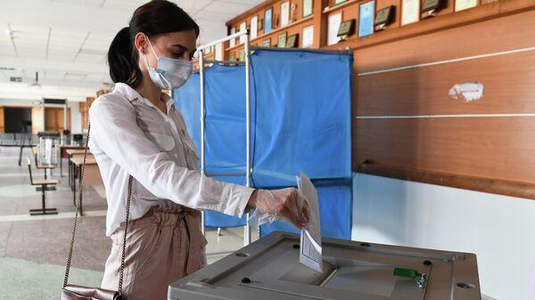 Девушка опускает бюллетень в урну во время демонстрации работы модельного участка для общероссийского голосования по поправкам в Конституцию РФ