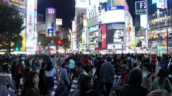 Люди на оживленном перекрестке района Сибуя в Токио