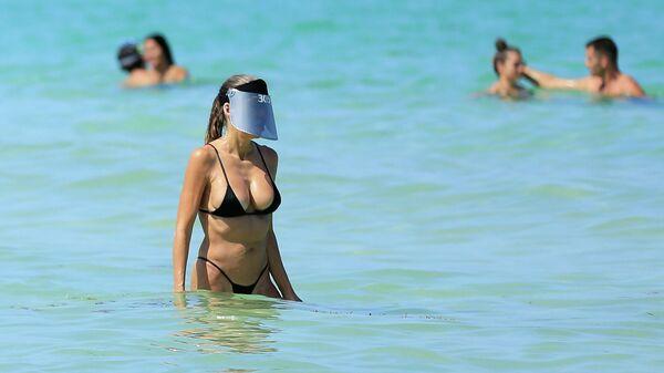 Девушка купается в океане в Майами-Бич, Флорида
