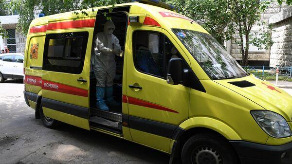 Фельдшер скорой медицинской помощи подстанции No 34 в Москве одевает средства индивидуальной зашиты перед посещением пациента с подозрением на коронавирус