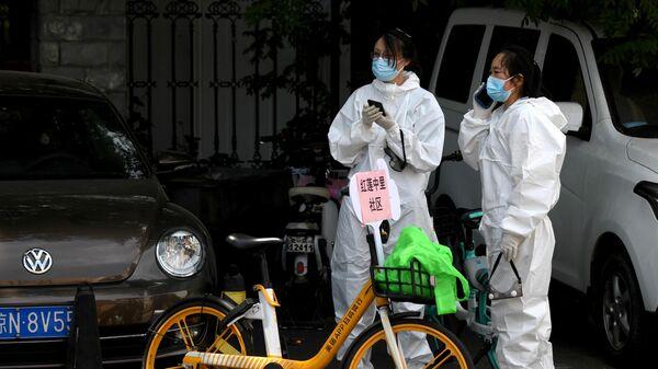 Девушки в защитных костюмах рядом с местом, где берут тест мазок на коронавирус у людей живущих рядом или посещающих рынок Синьфади