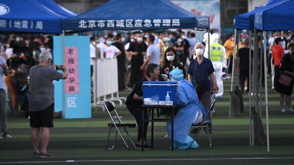 Тестирование людей на коронавирус, живущих рядом или посещающих рынок Синьфади в спортивном центре Guang'an в Пекине, Китай