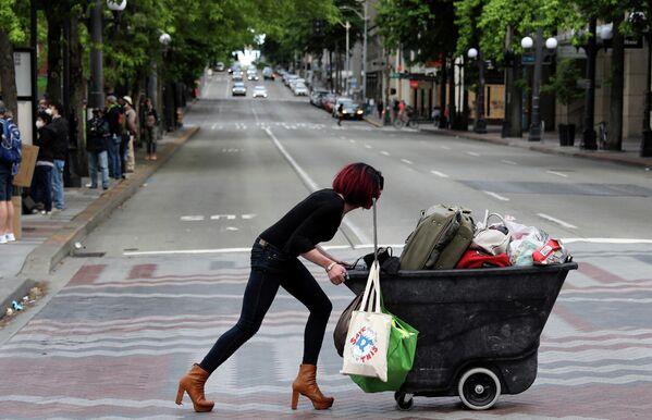 Женщина толкает телегу во время акции протеста против расового неравенства в центре Сиэтла, США