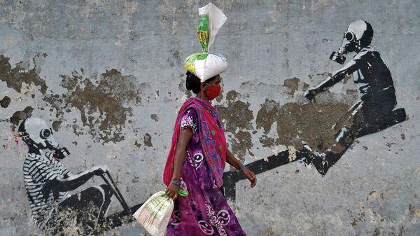Женщина в защитной маске проходит мимо граффити после ослабления карантинных мер в Мумбаи