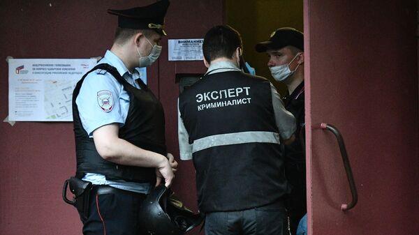 Сотрудник полиции и эксперт криминалист у жилого дома на севере Москвы, где мужчина открыл стрельбу