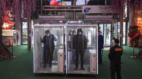 Посетители проходят через кабины дезинфекции при входе в торговый центр Европейский