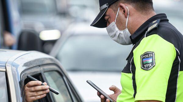 Полицейский проверяет документы у водителя автомобиля в Баку