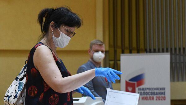 Женщина голосует по одобрению внесения поправок в Конституцию РФ на избирательном участке № 145 в Москве