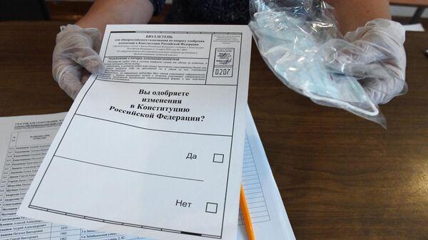 Сотрудник избирательного участка в Чите демонстрирует бюллетень для голосования по одобрению внесения поправок в Конституцию РФ