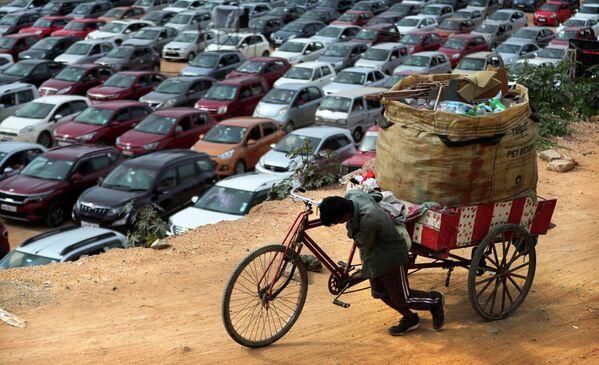 Мужчина толкает свой велосипед возле въездной мессы в церкви Bethel AG в Бенгалуру, Индия