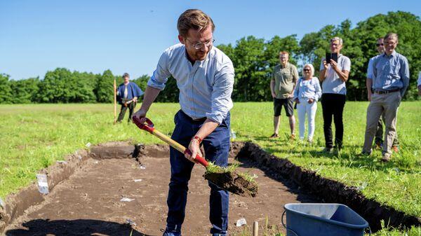 Министр климата и окружающей среды Норвегии Свейнунг Ротеватн начинает раскопки корабля викингов, обнаруженного в земле около Халдена