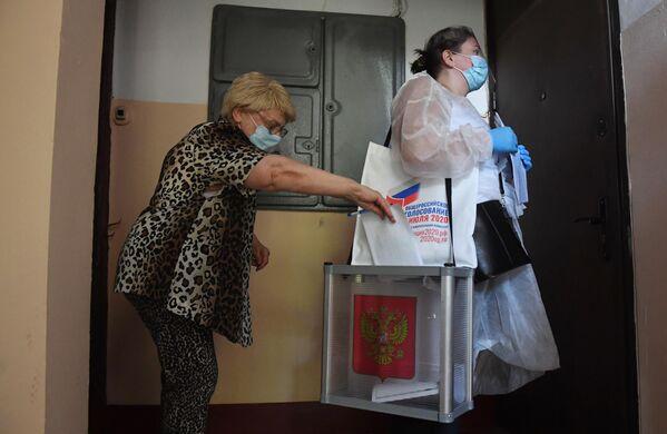 Женщина голосует по вопросу принятия поправок в Конституцию РФ у себя дома в Москве