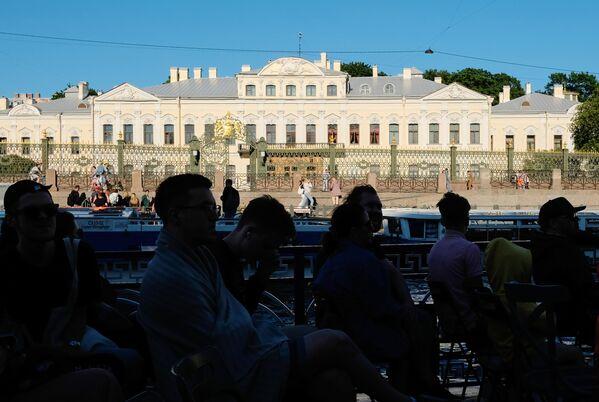 Туристы на прогулочном катере у Шереметьевского дворца в Санкт-Петербурге