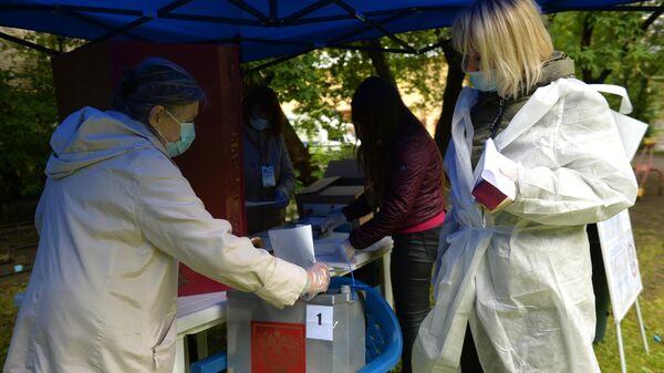 Женщина опускает бюллетень в переносную урну для голосования на избирательном участке №1409 на придомовой территории в Екатеринбурге во время голосования по внесению поправок в Конституцию РФ