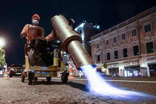 Сотрудники коммунальной службы наносят временную дорожную разметку на Тверской улице