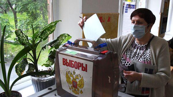 Женщина голосует по вопросу внесения поправок в Конституцию РФ на избирательном участке во Владивостоке