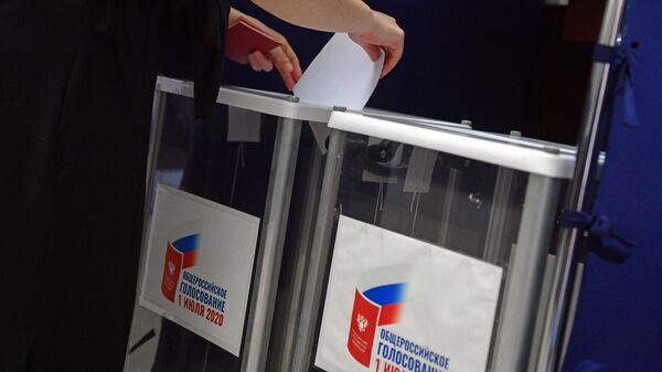 Женщина опускает бюллетень в урну для голосования на избирательном участке