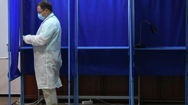 Мужчина голосует по вопросу одобрения изменений в Конституцию России на избирательном участке №1954 в Новосибирске