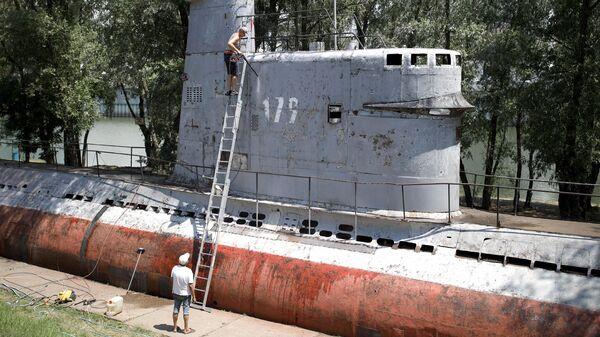 Местные жители чистят корпус малой многоцелевой дизельной подводной лодки М-261, установленной в парке 30-летия Победы в Краснодаре