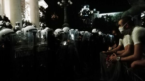 Полицейские и участники акции возле здания Парламента Сербии в Белграде после введения комендантского часа