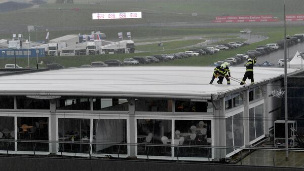 Firefighters remove water from the roof of the pit lane building during heavy rain during the third practice session for the Formula One Styrian Grand Prix on July 11, 2020 in Spielberg, Austria. (Photo by JOE KLAMAR / various sources / AFP)