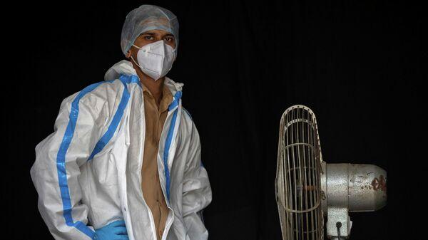 Медицинский работник в средствах индивидуальной защиты на перерыве в Нью-Дели, Индия