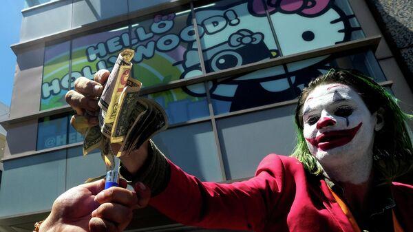 Участник акции протеста против политики Дональда Трампа в костюме Джокера сжигает долларовые банкноты на Аллее славы в Голливуде, США