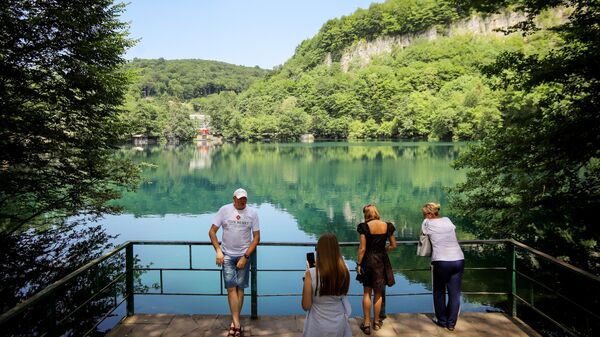 Туристы около Нижнего Голубого озера в Черекском ущелье в Кабардино-Балкарии