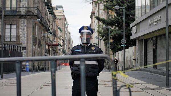 Полицейский в защитной маске на улице Мехико