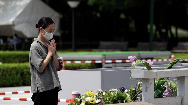 Женщина молится перед кенотафом о жертвах атомной бомбардировки в Хиросиме