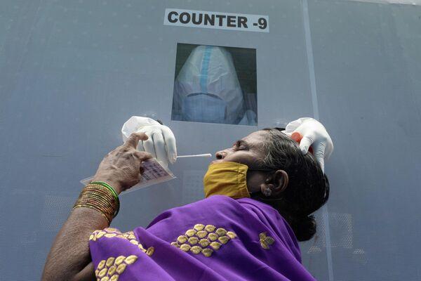 Женщина в мобильном пункте сдачи теста на коронавирус в Хайдарабаде, Индия