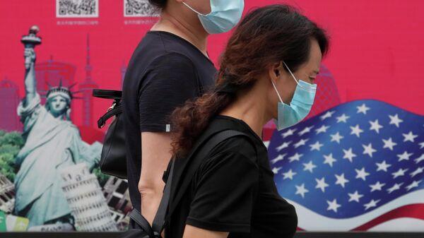 Женщины в защитных масках проходят мимо рекламного щита в Пекине