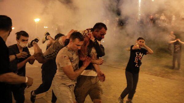 Протестующие несут раненого мужчину во время столкновений с полицией после президентских выборов в Минске