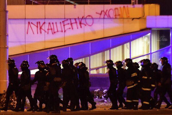 Сотрудники правоохранительных органов проходят мимо здания с надписью Лукашенко уходи! во время массовой акции протеста после президентских выборов в Минске, Беларусь