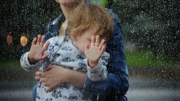 Женщина с ребенком на остановке общественного транспорта в Москве во время дождя