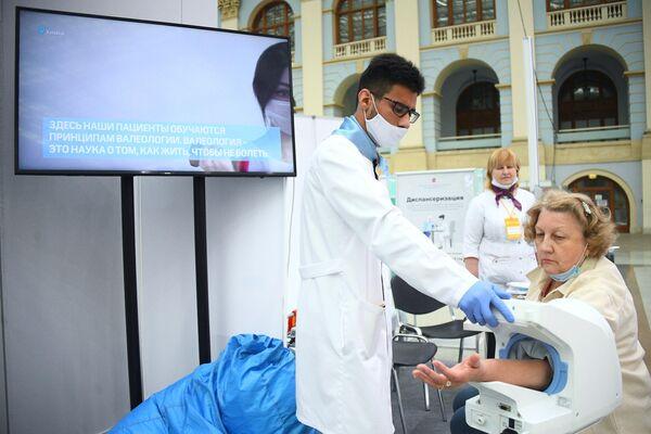 Женщина использует аппарат для измерения артериального давления на выставке всероссийского форума Здоровье нации  основа процветания России