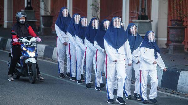 Студенты с защитными щитками маршируют во время забега в преддверии Дня независимости в Банджармасине, Индонезия