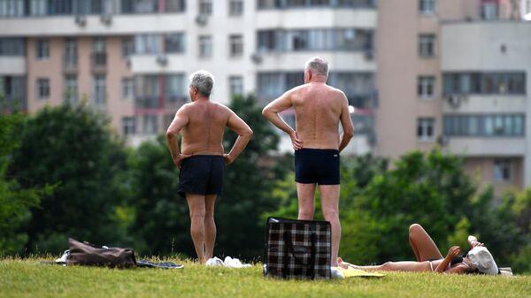 Люди отдыхают в жаркий день в парке на Ходынском поле в Москве